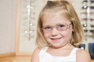 Young girl trying on eyeglasses at optometrists smiling